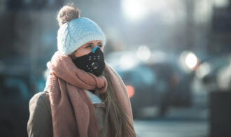 Young Woman Wearing Protective Mask In The City Street, Smog And Air Pollution